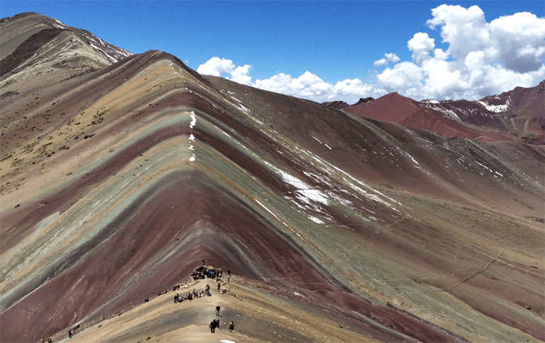Vinicunca rainbow mountain with blue sky and clouds