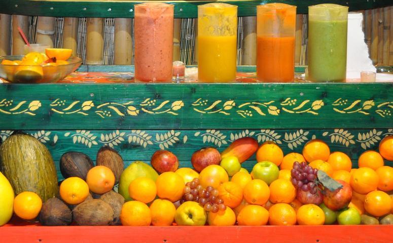 vier fruchtsaefte mit fruechten auf tisch