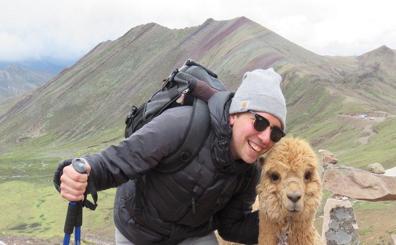 Lachender Reisender mit Alpaka am Palccoyo