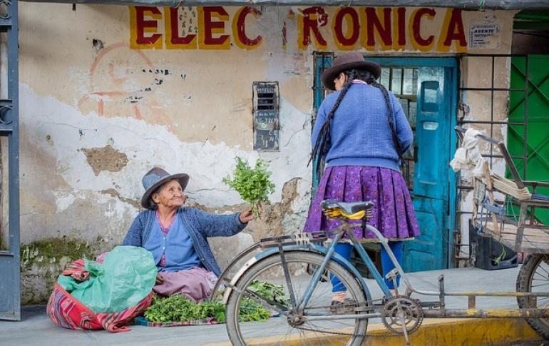 Mujer en calla vendiendo hierbas a otra mujer