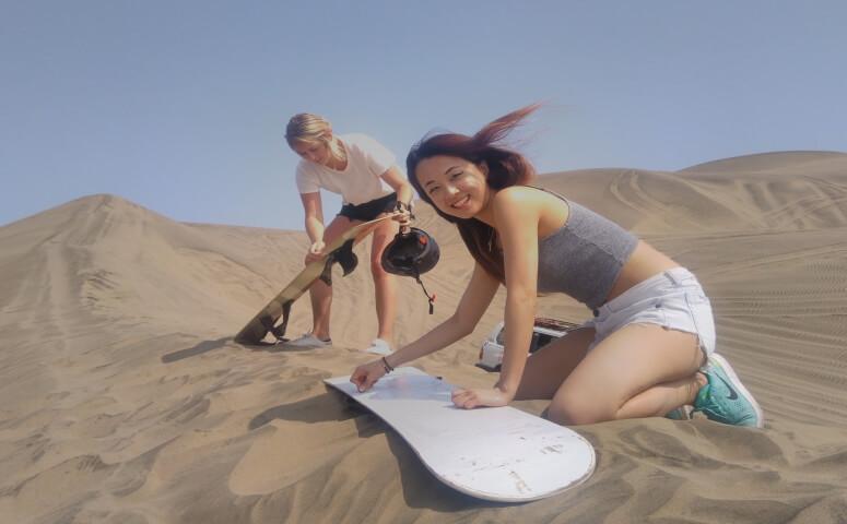 Dos chicas preparandose para sandboarding en desierto