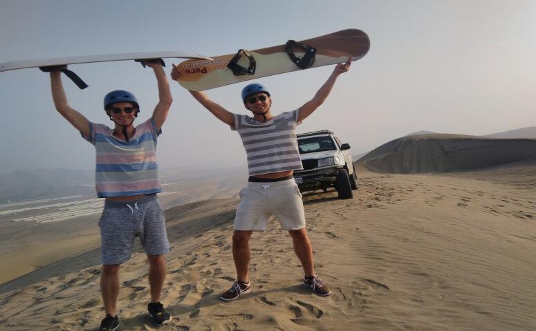 Dos amigos en desierto con sandboards y jeep