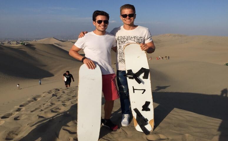 Dos amigos en desierto con sandboards