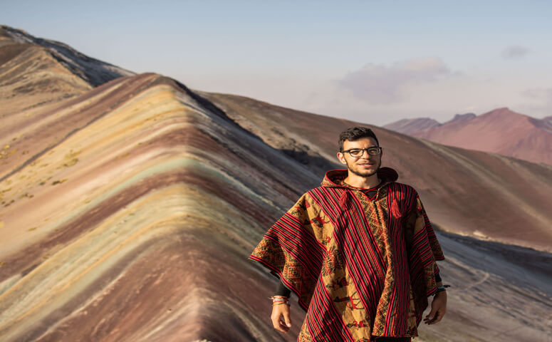 traveler with glasses and poncho at rainbow mountain vinicunca