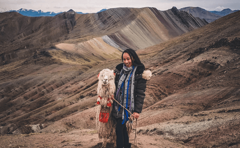 girl with alpaca in front of rainbow mountain palccoyo