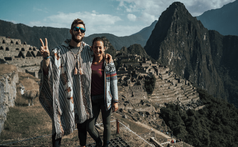happy travelers with ponchos at machu picchu ruins