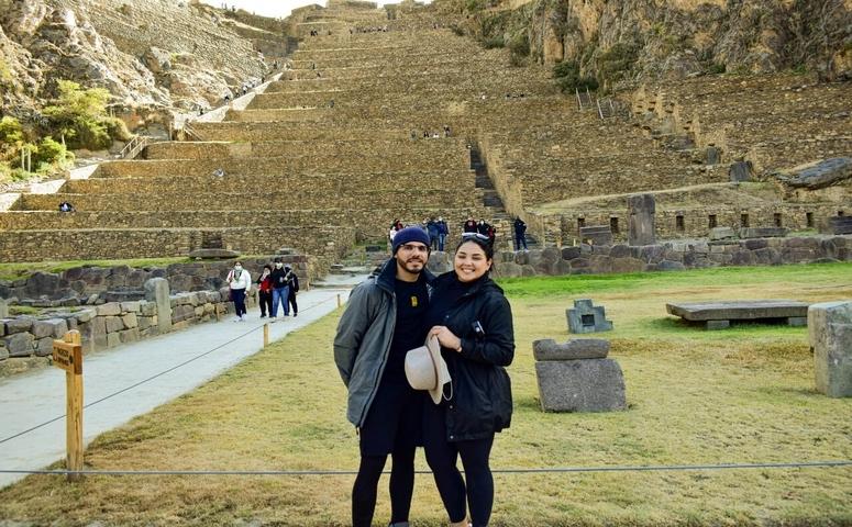 couple at ollantaytambo ruins and travelers background