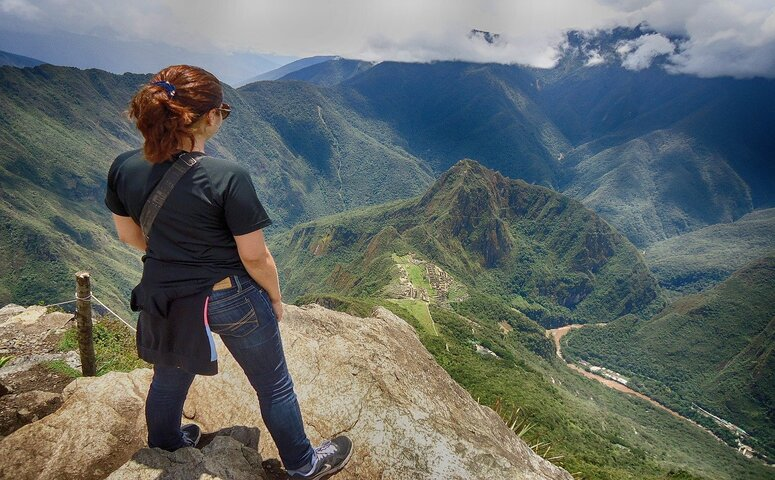 girl looking on ruins from machu picchu mountain