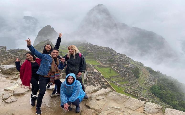 five travelers in front of cloudy machu picchu
