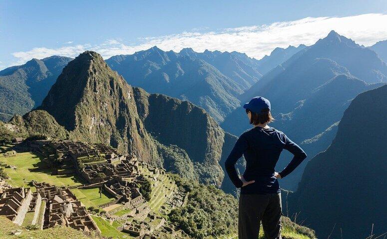 woman in cap standing at machu picchu
