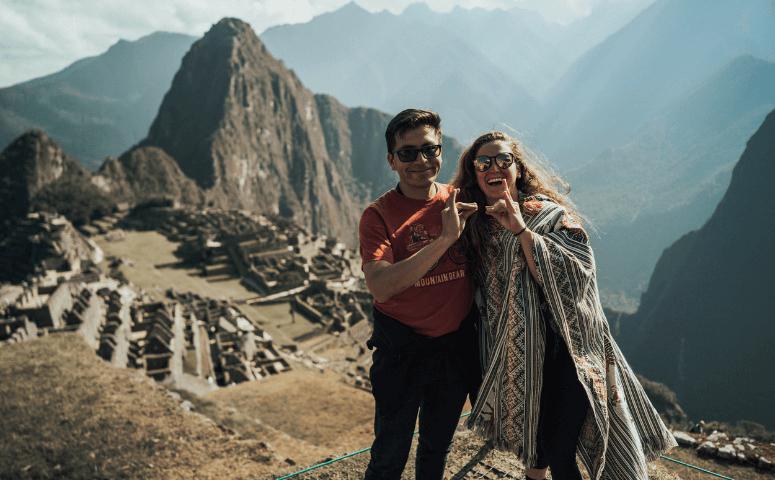 hombre y mujer con poncho en machu picchu